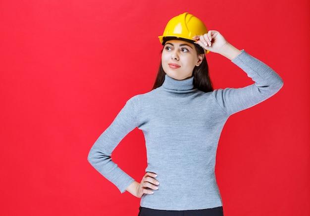 Meisje in gele helm die haar helm vasthoudt en poseert.