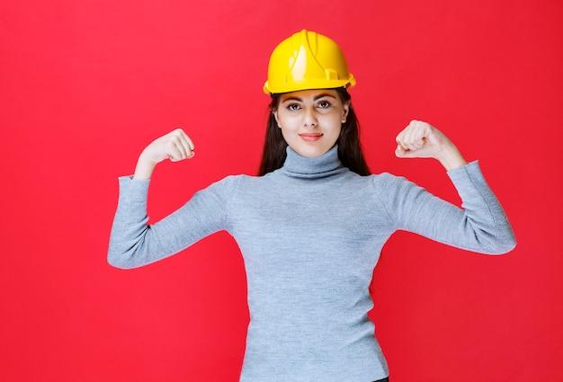 Meisje in gele helm die zich positief voelt.