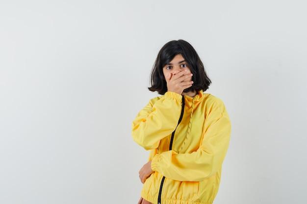 Meisje in gele hoodie die hand op mond houdt en verbaasd, vooraanzicht kijkt.