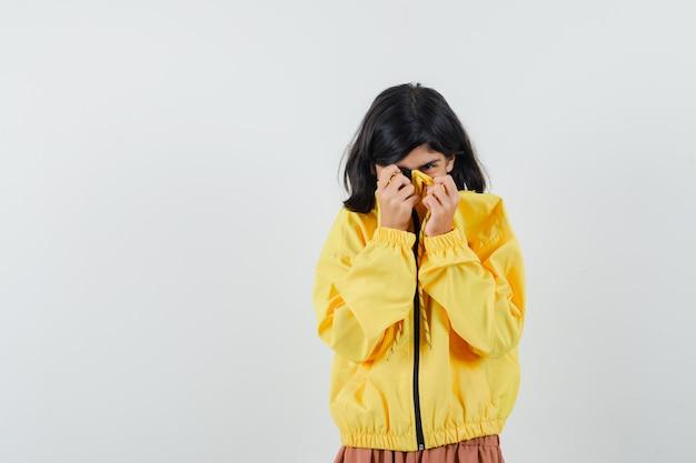 Meisje in gele hoodie trekt haar kraag op gezicht en kijkt bang, vooraanzicht.