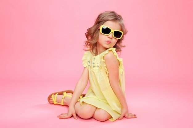 Meisje in gele jurk en zonnebril