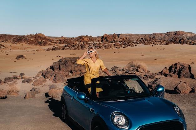 Meisje in gele jurk genieten van een road trip in een cabrio door een verlaten vallei met bergen, canarische eilanden, tenerife.