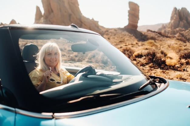 Meisje in gele jurk genieten van een roadtrip in een cabriolet door een verlaten vallei met bergen, canarische eilanden, tenerife.