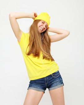 Meisje in gele t-shirt die met geïnspireerde gezichtsuitdrukking dansen. actieve jonge vrouw in casual zomer outfit plezier binnenshuis