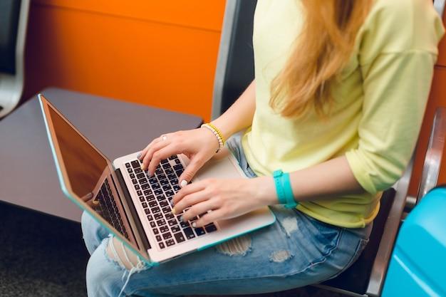 Meisje in gele trui en spijkerbroek zit op een stoel. ze heeft een laptop op de knieën. focus op typen met de hand op laptop.