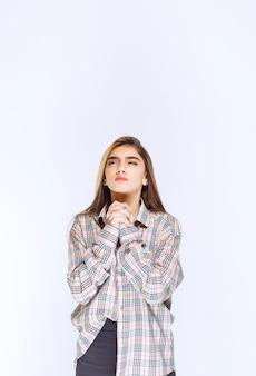 Meisje in geruit overhemd dat handen verenigt en bidt