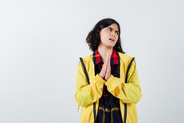 Meisje in geruit overhemd, jasje dat bidgebaar toont en hoopvol kijkt