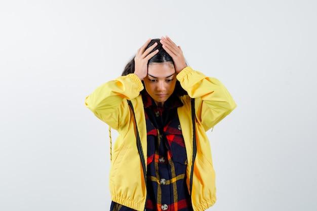 Meisje in geruit overhemd, jasje hand in hand op het hoofd en vergeetachtig op zoek