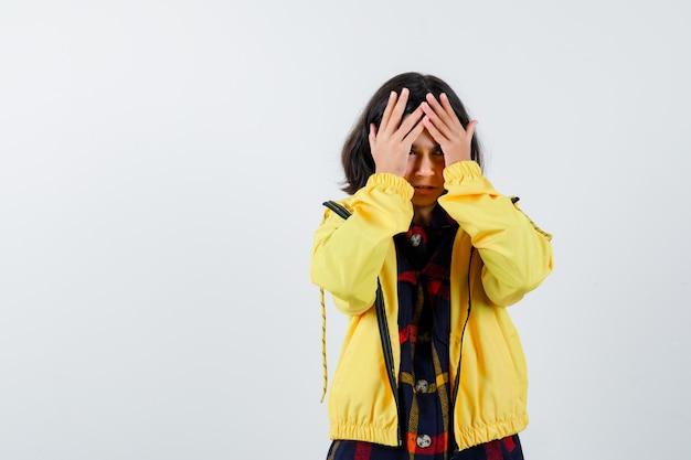 Meisje in geruit overhemd, jasje hand in hand op voorhoofd en vergeetachtig op zoek