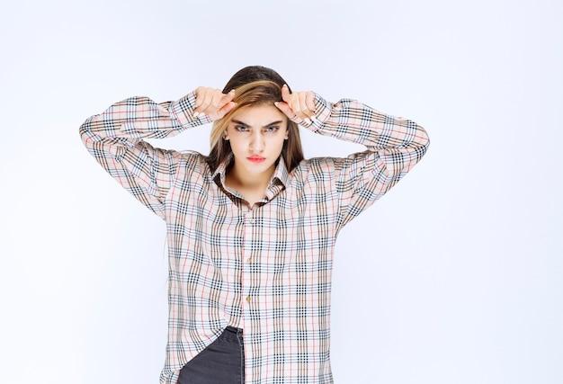 Meisje in geruit overhemd maakt ossenhoorns