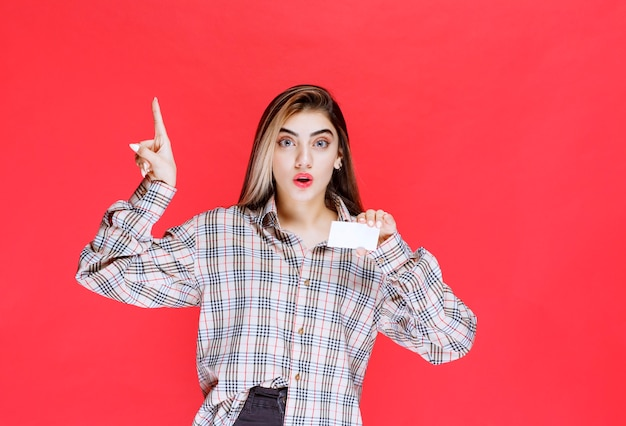 Meisje in geruit overhemd met een visitekaartje en kijkt verrast