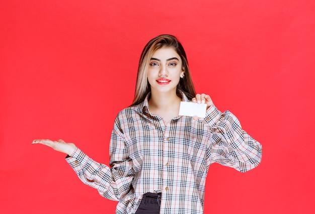 Meisje in geruit overhemd met een visitekaartje en wijzend naar haar collega