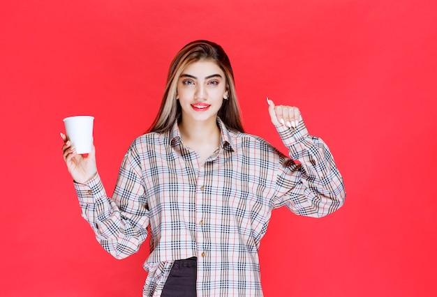 Meisje in geruit overhemd met een wit wegwerpkoffiekopje en toont haar kracht
