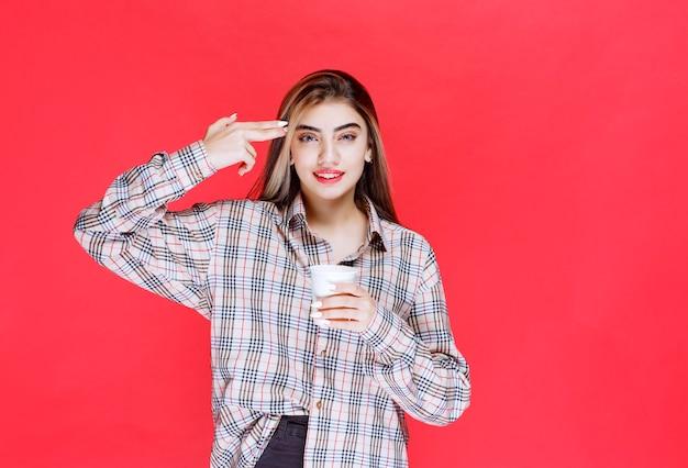 Meisje in geruit overhemd met een wit wegwerpkoffiekopje en ziet er attent uit of heeft goede ideeën