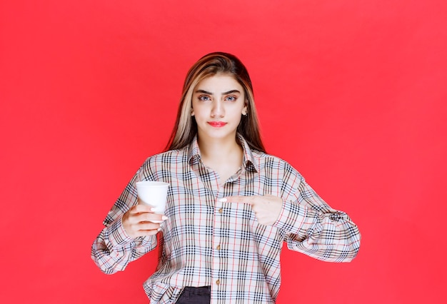 Meisje in geruit overhemd met een wit wegwerpkoffiekopje
