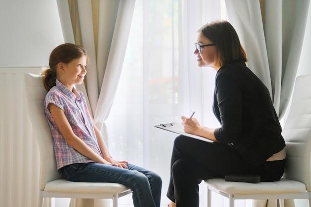 Meisje in gesprek met vrouw counselor psycholoog bespreken van de gevoelens van het kind