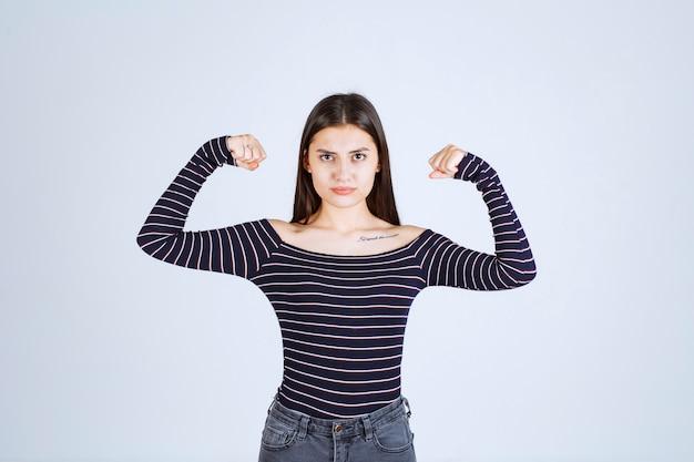 Meisje in gestreept overhemd dat haar armspieren aantoont.