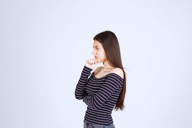 Meisje in gestreept overhemd denken en analizing.