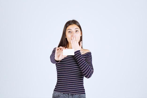 Meisje in gestreept overhemd houdt een visitekaartje vast en kijkt verbaasd.