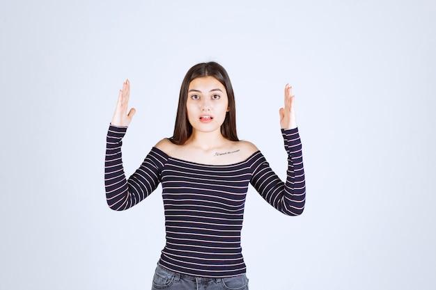 Meisje in gestreept overhemd met de geschatte maat of hoeveelheid van een product.
