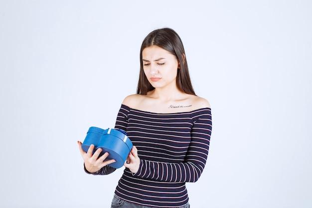 Meisje in gestreept overhemd met een blauwe hartvormige geschenkdoos en wordt opgewonden.