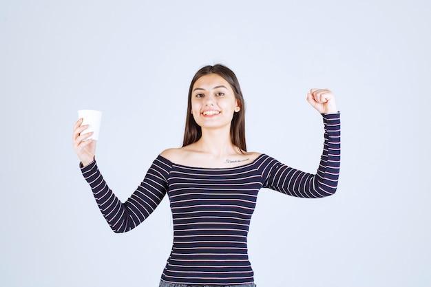 Meisje in gestreept overhemd met haar armspier en vuist.