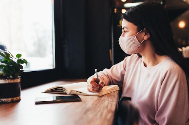 Meisje in gezichtsmasker, kijken in venster, schrijven in notitieblok. onscherpe achtergrond. hoge kwaliteit foto
