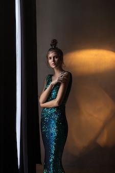 Meisje in glanzende groen-blauwe jurk staat in warm licht, rook,