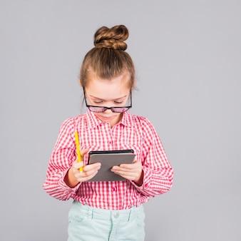 Meisje in glazen die tablet gebruiken