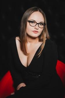 Meisje in glazen en een zwarte jurk in een rode stoel op een zwarte muur