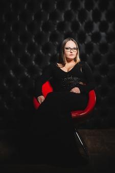 Meisje in glazen en een zwarte jurk in een rode stoel