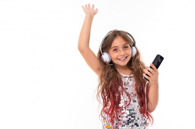 Meisje in glitter jurk, met grote witte koptelefoon en zwarte mobiele telefoon in haar hand zwaaien naar iemand geïsoleerd