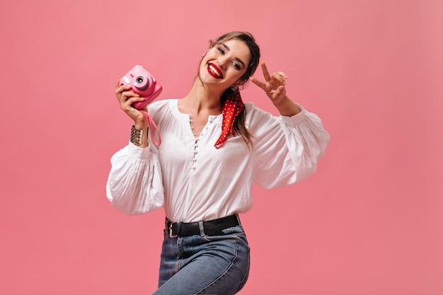 Meisje in goed humeur houdt camera vast en toont vredesteken op roze achtergrond. mooie dame met rode lippenstift in witte blouse en spijkerbroek lacht.