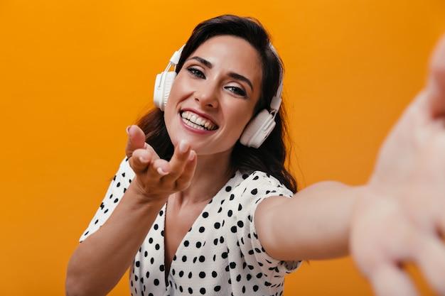 Meisje in goed humeur luistert naar muziek met een koptelefoon en neemt selfie op een oranje achtergrond