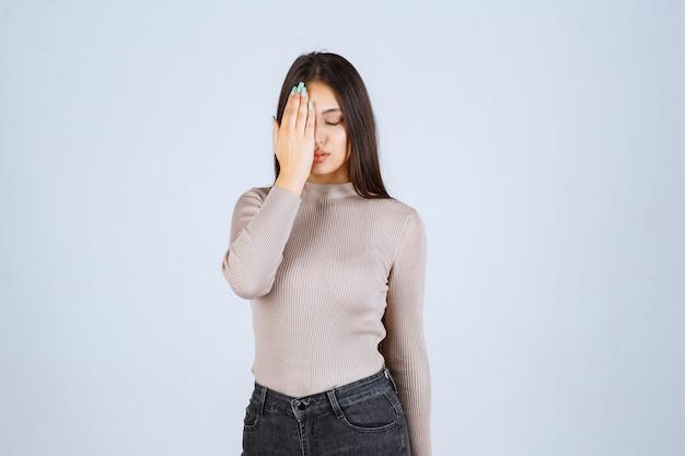 Meisje in grijs overhemd dat haar gezicht met hand sluit.