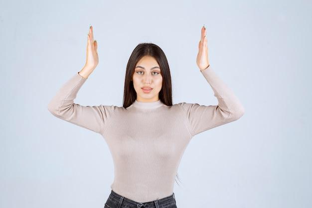Meisje in grijs overhemd dat haar handen opheft.