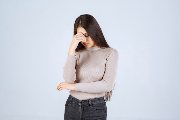 Meisje in grijs overhemd dat haar hoofd wegens hoofdpijn houdt.