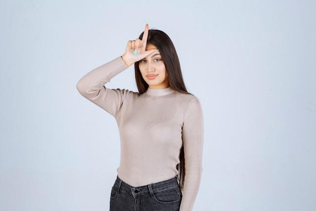 Meisje in grijs overhemd dat het teken van de verliezerhand toont.