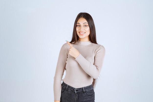 Meisje in grijs overhemd dat hierboven iets laat zien en opgewonden raakt.