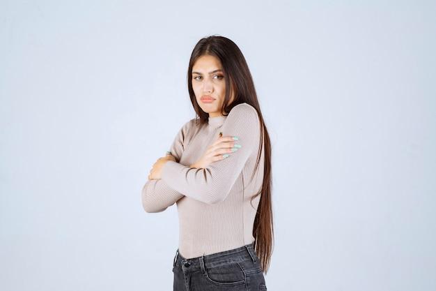 Meisje in grijs overhemd dat koud voelt.