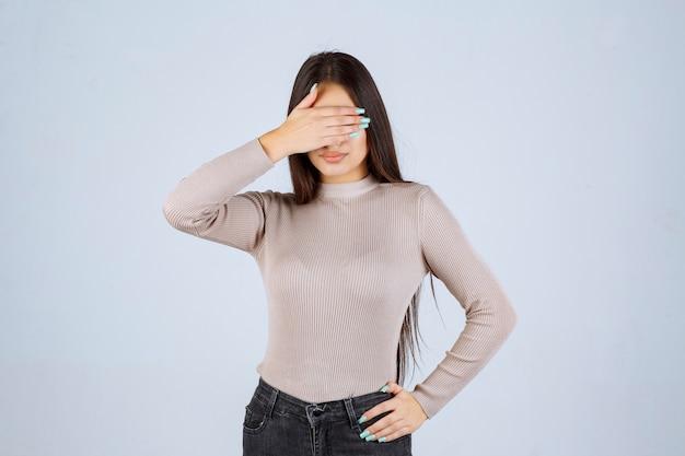 Meisje in grijs overhemd die en haar gezicht bedekken.