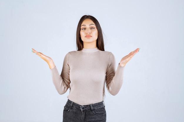 Meisje in grijs overhemd met de geschatte afmetingen van een object.