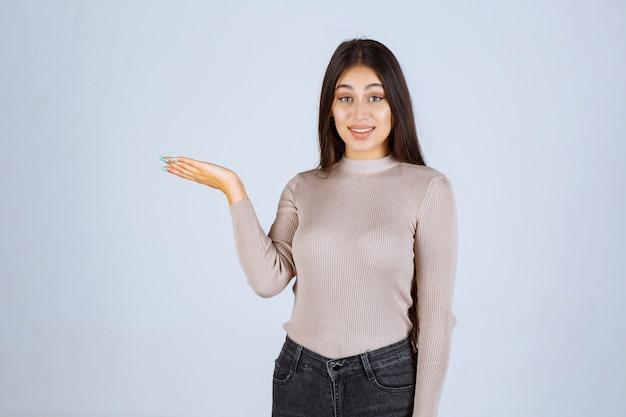 Meisje in grijs overhemd met iets in haar hand.