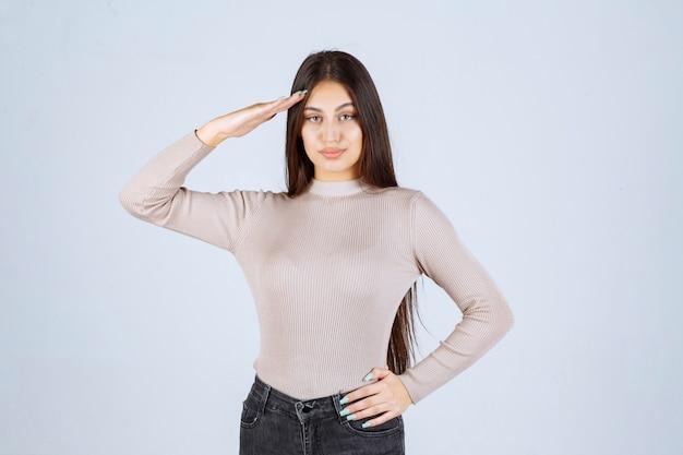 Meisje in grijs overhemd salueert als een soldaat.