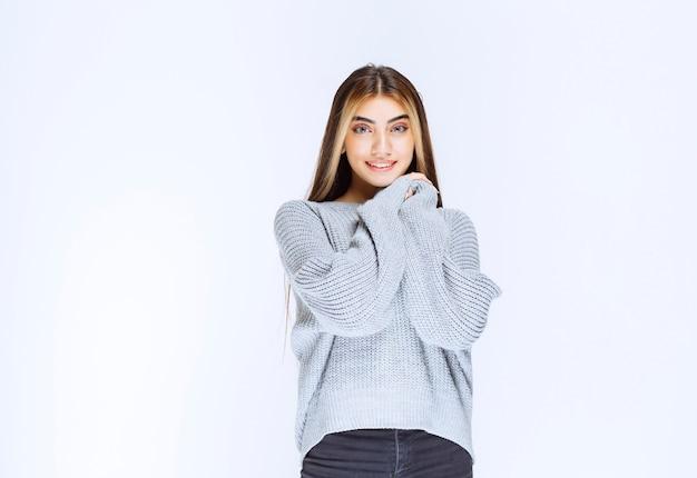 Meisje in grijs shirt voelt zich vredig en gelukkig.