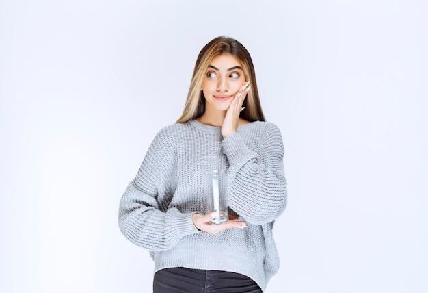 Meisje in grijs sweatshirt dat een glas zuiver water vasthoudt en een twijfelend gezicht trekt. Gratis Foto