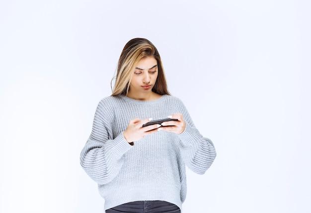 Meisje in grijs sweatshirt dat een zwarte smartphone vasthoudt en een bericht of een opmerking schrijft.