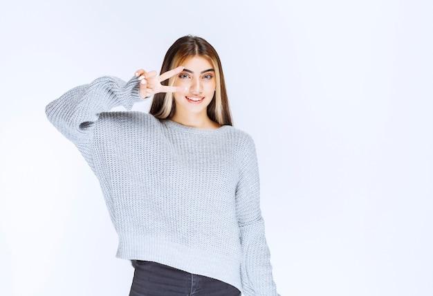 Meisje in grijs sweatshirt dat vrede en vriendschapsteken toont.