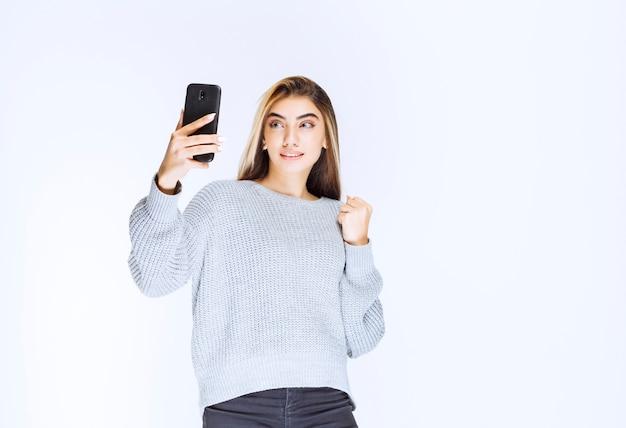 Meisje in grijs sweatshirt met een zwarte smartphone en tevreden.