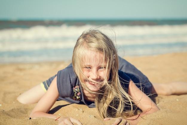 Meisje in grijze kleding die pret heeft die op het zand tegen het overzees ligt.